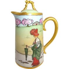 Antique French Limoges Tea Pot with Whimsical Figural Scene. D&C Limoges teapot featuring a lady dressed in her Sunday best complete with hat and green umbrella walking a stone path leading to cozy brown house. Gold Gilt. Hand painted porcelain, France, circa 1894 - 1900. Late 19th century teapot or chocolate pot.