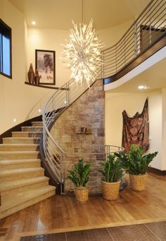 Check out this two story foyer with a stone wrapped circular stairway, brushed chrome railing and crocodile leather tile inset. Comito Building and Design, LLC