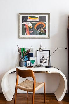 a midcentury chair tucks into a Jetsonian lacquered-wood desk under a bold Russian abstract.