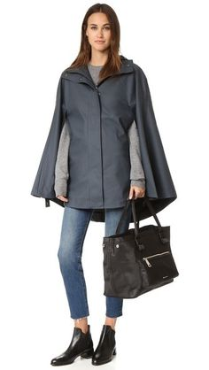 A hooded Hunter rain cape with a matte finish. Snaps fasten the arm openings, and a zip closes the center. Mesh lining.