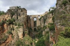 Puente Nuevo Bridge in Ronda, Spain. Built on an dramatic isolated ridge, the town of Ronda is split in half by a gaping river gorge, whose sheer cliffs drop over 400 feet on three sides. The gorge is spanned by an eighteenth-century arched bridge, the Puente Nuevo, that looks like it came straight out of an adventure fantasy, while tall, picturesque houses lean from its precipitous edges.
