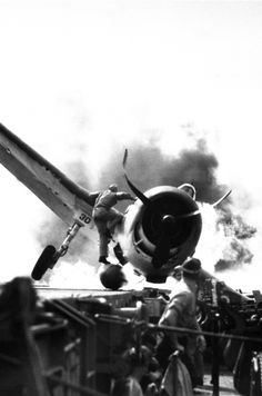 "Crash landing of Grumman F6F Hellcat on flight deck of USS Enterprise while enroute to attack Makin Island during the ""Battle of Makin."" Lt. Walter Chewning the catapult officer is clambering up the side of the plane to assist pilot Ens. Byron Johnson, from the flaming cockpit, November 1943."