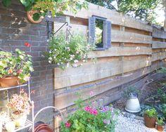 Sfeervolle tuin met tuinafscheiding van lariks douglas schaaldelen.