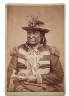 """Albumen Cabinet Card: Apache Chief """"Yan-hah"""" Photograph. by W. P. Bliss of Fort Sill, Indian Territory c. 1879. He wears an Army musician's hat, jackets with shoulder boards, a large silver cross, and he holds a heart cut-out pipe tomahawk. Bliss' studio imprint and pencil title verso. A very desirable image. From the estate collection of E.F. Mueller."""