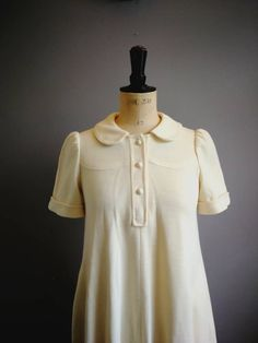 Vintage 70s cream swing dress. A perfect winter dress.   FIT: UK 10 - 14.  🌵 70s vintage dress. 🌵 Thick polyester. 🌵 A line swing shape. 🌵 Peter Pan collar. 🌵 Pockets. 🌵 Three cream buttons.  CONDITION: very good. Some discolouration on the buttons. Small mark near top.  Bust: 34