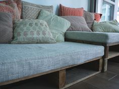 Living room sofa?  Stain pallets dark, but use a bed ruffle to soften.  Twin mattress for seating cushion.
