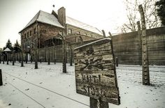 """The fence of the Auschwitz I camp. You can see two lines of barbed wire fence which was electrified. Prisoners were not allowed to get close to the fence, that is why the """"Halt"""" sign was there. Behind the wall the building of the so-called Old Theatre is visible. We hope that in the future it will be our Education Center."""