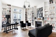 This apartment, with its wrought iron balcony railing and floor-to-ceiling bookshelves is indicative of the French way of life. Reading, relaxing, and celebrating beauty. The black furnishings are another popular theme throughout these French homes.
