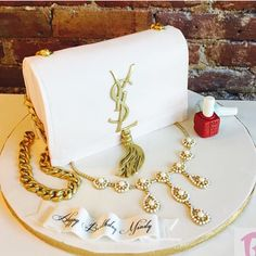 YSL purse cake with sugar necklace and Essie Polish, all edible ! TAG 3 friends whose bag, Jewelry and nail game is on point, always on FLEEK !! Cake by @bcakeny #NWcakes #NigerianWedding