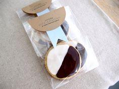 インパクトのあるアイシングクッキーのラッピング。丸く切ったクラフト紙でリボンを挟んでいます。中身の見えるセロファンを使うことで、より可愛くインパクトのあるものに。
