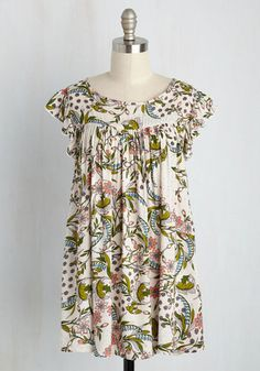 Teamed up with this vintage-inspired blouse, your beautiful voice silences the audience. Setting a soothing tone, the creamy background, field of pastel flowers, and green vines on this flowing top elevate your stage presence. With ruffled shoulders and a tasseled back tie, this sweet style is your pretty partner in crime!