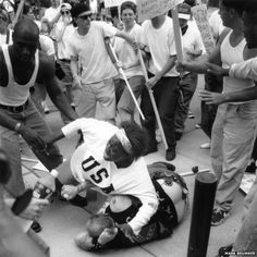Keshia Thomas, then 18, protecting a man dressed in confederate flag at an anti klan protest. One of the more inspiring images I've ever seen.