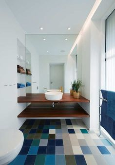 A gorgeous mosaic of blue and neutral tiles makes this all-white bathroom in the Villa Midgard house, designed by DAPstockholm, sing. http://design-milk.com/creative-tile-floors/