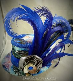 Ziggy Medi Topper #DHMD06 Mini top hat fascinator inspired by Bowie's other worldly style. Covered with a multi colored psychedelic galaxy pattern the fabric is overlaid with metallic silver stars. I paired it with a royal blue velvet band and a handmade silver centerpiece made from small mirrors and a royal blue rhinestone brooch finished with royal blue and purple feathers. www.darecrafts.com  #darecrafts #creativelife #inspiration #costuming #divergent #embellishments