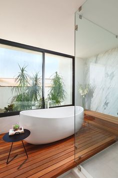 In this modern bathroom, a freestanding white bathtub is positioned in front of the window on a raised wood platform.