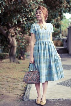 Vintage dresses always run the risk of appearing too dated but, in this instance, I love how the adorable plaid dress is modernized by the side-swept up-do, printed handbag, and glistening peter pan collar.