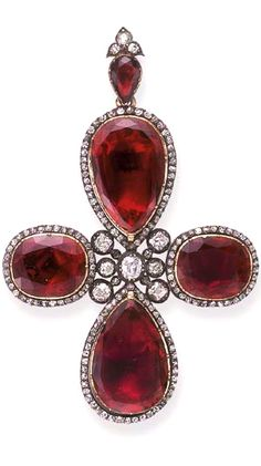 AN ANTIQUE GARNET AND DIAMOND CROSS PENDANT  Centering upon an old mine, cushion and single-cut diamond openwork plaque, extending foil-backed pear and oval-cut garnets, each within a single-cut diamond surround, suspended by a similarly-designed bail, mounted in silver and gold, (with damage to reverse), early 19th century