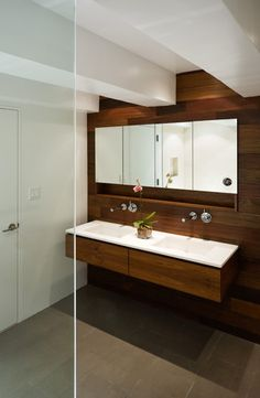 wood wall and vanity, tile floor, white counter. Mirror with niche shelf below