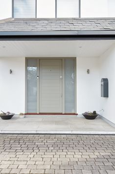 Light floods the interior space of this home, thanks to the door's full-length sidelights. The plain, opaque glazing works in sympathy with the minimalist features. Contemporary, Grey Doors, Minimalist, Outdoor Decor, 21st Century Homes, Contemporary Front Doors, Home, Front Door, Home Decor