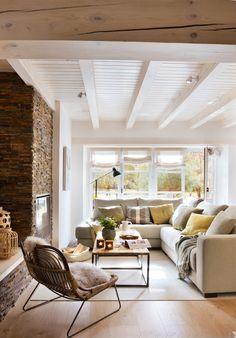 Salón rústico con vigas blancas, sofá en L de línea recta, mesa de hierro y madera. Pared de piedra. Chimenea (417802)