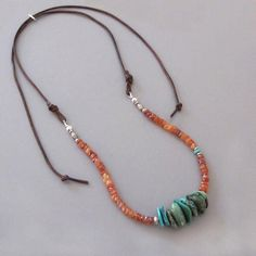 natural organic Turquoise chips surrounded by beautiful Carnelian nuggets and handmade fine silver beads are wrapped to a brown leather cord. A tiny Arizona Kingman mine turquoise sits off to one side. I bought the chips in New Mexico almost 20 years ago. It adjusts with a silver slide to