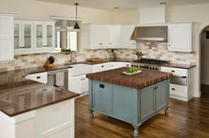 Muralo Paints modern kitchen blue island. The layout of this kitchen is wonderful and the blue cabinet between the white is a great contrast.