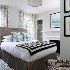 Rachel Reider Interiors - bedrooms - sage green paint, sage green walls, bed in front of windows, fretwork rug, blue fretwork rug, gray headboard, gray linen headboard, black and white, black and white throw, turquoise blue coral pillows, coral pillows, black pedestal table, grommet drapes, ikat chair, gray bed skirt, blue glass lamp, geometric window panels, geometric grommet drapes, patterned curtains, gray and blue bedroom, blue and gray bedroom, black throw, , Grecian Maze Dhurrie Rug…