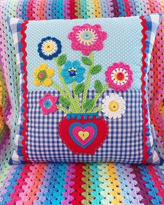 Beautiful handmade colourful applique patchwork cushion, embellishished with a heart shaped vase full of  cute crocheted flowers.