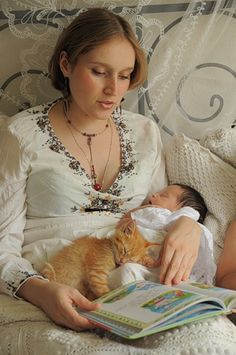 Mama reading to baby and kitten; passing on a loving tradition!