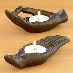 Aluminum Hand Tealight Holders. Designed with intricate etchings, one Buddha-inspired hand features all five fingers outstretched in a traditional pose of giving charity, while the other features the index finger and thumb touching in the classic teaching pose.