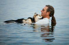 Un perro de 19 años de edad llamado Schoep es mecido por su amo, John, en las aguas del lago Superior, en donde la flotabilidad alivia el dolor del perro, lo que le permite dormirse cómodamente en los brazos de su amo. i