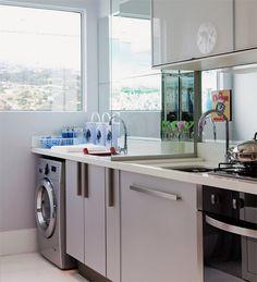 Em apenas 2 m², a sensação de amplitude foi alcançada graças ao vidro (45 cm x 1,50 m, Comovil), que separa os ambientes sem bloquear a luz, e ao espelho, aplicado acima da bancada de marmoglass. Os tons dos armários, com acabamento de laminado e vidro (Ornare), das paredes e do porcelanato favorecem a claridade.EquipamentoLavadora: WD8854RJZXAZ (Samsung) Capacidade: 8,5 kg Preço: 2 999 reais (lava e seca)