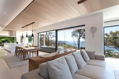 Open plan living united by a line of timber highlighting the fireplace and rising up and over t...