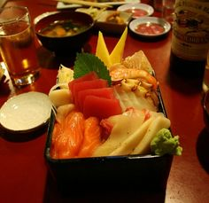 A Sashimi Bowl that has Rice covering the bottom.