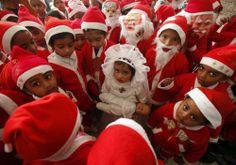 Niños vestidos de Santa Claus se reúnen alrededor de una niña vestida de Virgen maría.