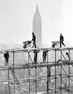 Construction en cours des bâtiments du siège des Nations Unies. En arrière plan, l'Empire State Building. New York, 6 décembre 1949.