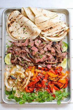 INGREDIENTS     * about 2 lb. skirt steak      * 2-3 bell peppers, ends trimmed, cored and seeded, cut into a couple       large pieces     * 1 large white onion, peeled and cut into 1/2-3/4-inch slices (keep       the slices intact)     * 18 6-inch flour tortillas     * lime wedges      * toppings of your choice such as, cilantro, salsa, cheese, sour cream        & avocados or guacamole  For the Marinade:      * 1/3 c. soy sauce     * 1/3 c. fresh squeezed lime juice     * 1/3 c. canola oil…