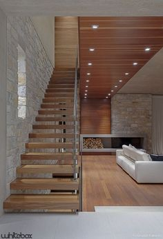 I love these kind of stairs that are open & light & very structural. And the juxtaposition of warm woods with the stone connected by the wood box/ fireplace. A great room overall!: