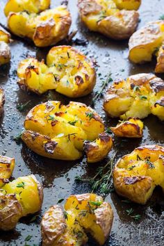 Smashed Potatoes baked with garlic, olive oil and herbs, fluffy in the middle and truly crispy on the top!! Get the recipe at noshtastic.com, it's gluten free, vegan, paleo, and whole30 compliant.