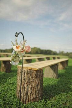 {ceremony} outdoors, logs & wood planks as bench seating