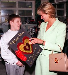 Diana, Princess of Wales receiving a hand-made Valentine's card from 16-year-old Paul Read, on behalf of the Dialysis Unit, during her visit to the Great Ormond Street Hospital in February 1997