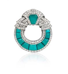 An Art Deco turquoise brooch of open circular design with scrolled diamond top…