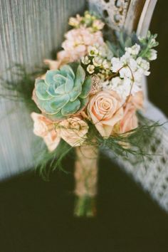 Beautiful bouquet hand tied with burlap and composed of white and peach stock, wax flower, spray roses and succulents.