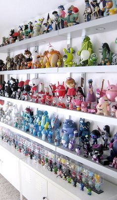 Wow. This must of taken awhile to collect. Collection of action figures, many by color, on white shelves on white walls