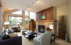 feng shui couleurs, plafond en bois, murs blancs, cheminée en pierre, canapé noir