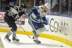 Tina Russell / Observer-Dispatch From left, San Antonio player Stephan Vigier defends as Utica Comets player Brandon DeFazio brings the puck down the rink during AHL hockey at the Utica Memorial Auditorium Thursday, Jan. 1, 2015. Read more: http://www.uticaod.com/apps/pbcs.dll/gallery?Site=NY&Date=20150101&Category=PHOTOGALLERY&ArtNo=101009998&Ref=PH&taxoid=&refresh=true#ixzz3Ndf2s0Wq