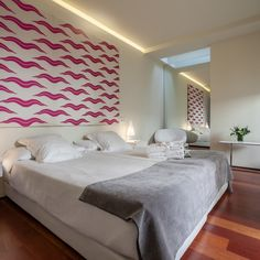 "Hotel viento 10 | Twin first floor.   through the skylight and the gallery facing the patio of columns, a glare takes hold of the room and shift in shades throughout the day.  a tapestry made in silk and inspired on the smile of budha lighten the head of the bed. tapestry ""tiger lines"" by rocío moreno.  the floor of the bathroom has a metallic silver finish in microcement."