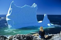 A woman sits on the rocks in the village of Twillingate, Newfoundland in Canada where an iceberg has beached itself. Laura Lee, Newfoundland Icebergs, Places To Travel, Places To See, East Coast Travel, Newfoundland And Labrador, Newfoundland Canada, Atlantic Canada, Canada Eh