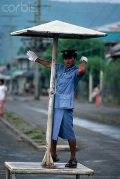 Traffic officer standing on a platform with an umbrella directing traffic in Apia, Western Samoa.