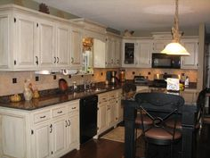 Shabby Chic Kitchen Idea with White Kitchen Cabinets and Rustic Black Island and Dark Color Granite Countertops also Antique Barstools and Beige Ceramic Backsplash and Black Appliances and Fake Wood Flooring Idea - Use J/K to navigate to previous and next images